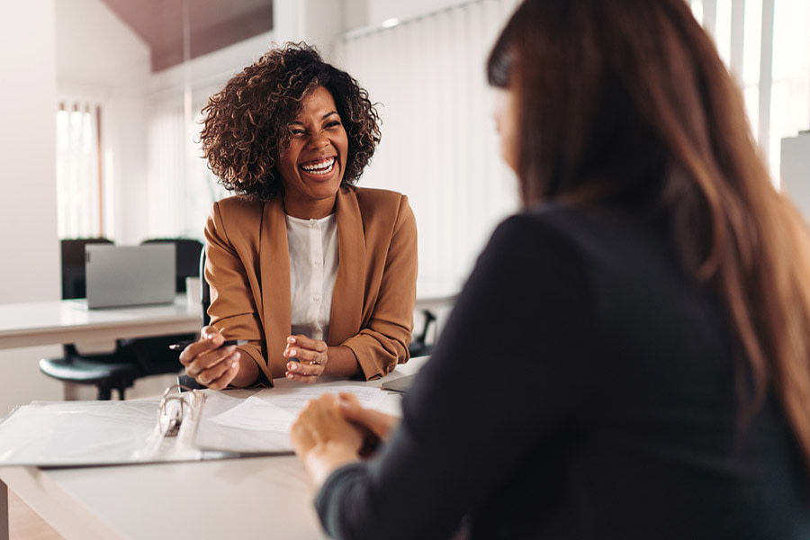 Two female treatment providers share a positive moment as they talk at work